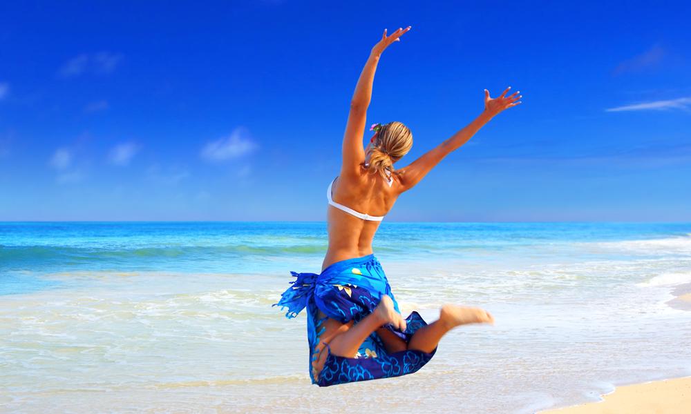 Gute Rhetorik lernen macht kommunikationsstark. So wie diese Frau, die vor Glück am Strand in die Luft springt.