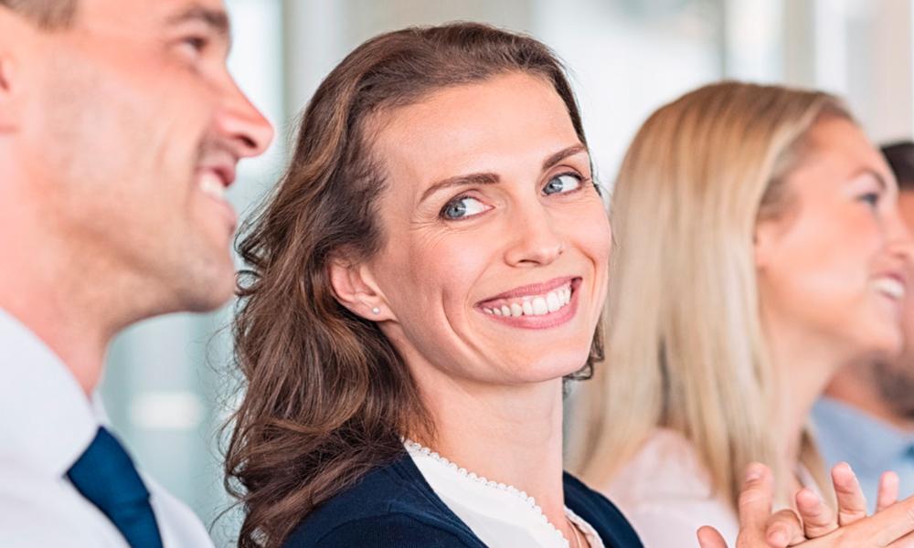 Frau in Businessoutfit lächelt Kollegen neben ihr an