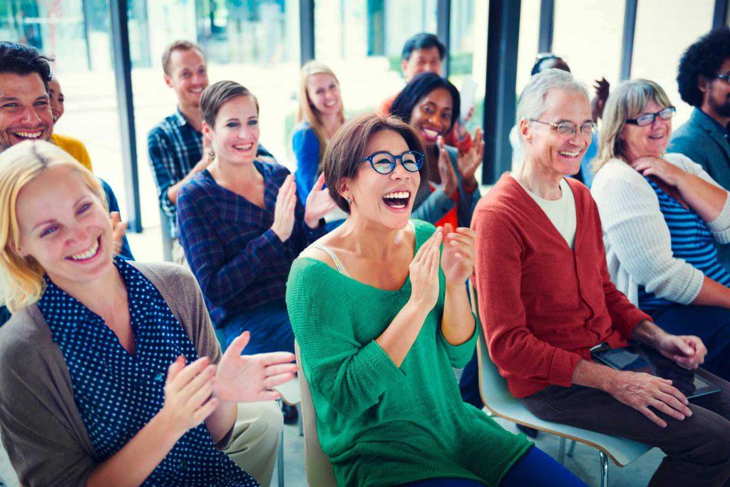 Gruppe klatschender Menschen mit begeisterten Blicken