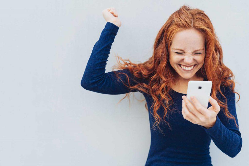 Frau mit Mobiltelefon freut sich, streckt Arm in die Luft und lacht